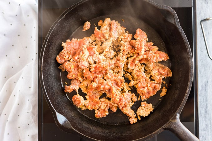 ground pork sausage being browned in a cast iron skillet
