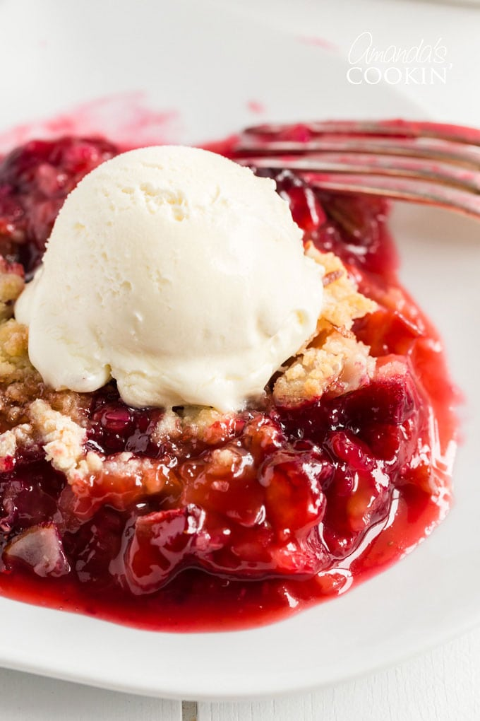 close up of rhubarb crumble with vanilla ice cream on a plate