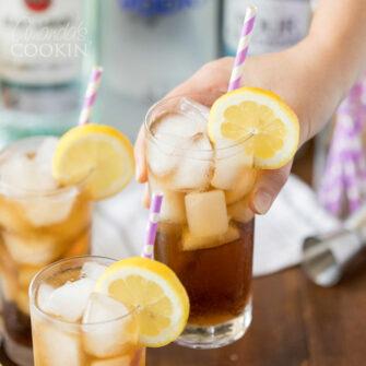 hand lifting a glass of Long Island Iced Tea