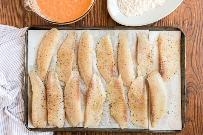 fish strips on paper towels seasoned with salt and pepper
