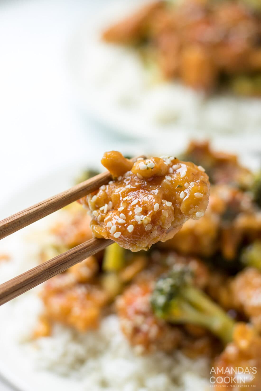 chopstick holding sesame chicken