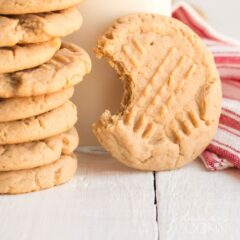 peanut butter cookie with a bite out of it with a stack of cookies and glass of milk