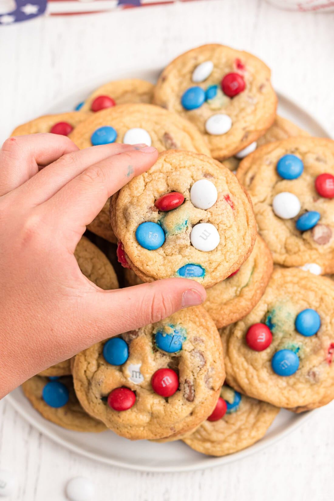 child taking a patriotic cookie from a plate