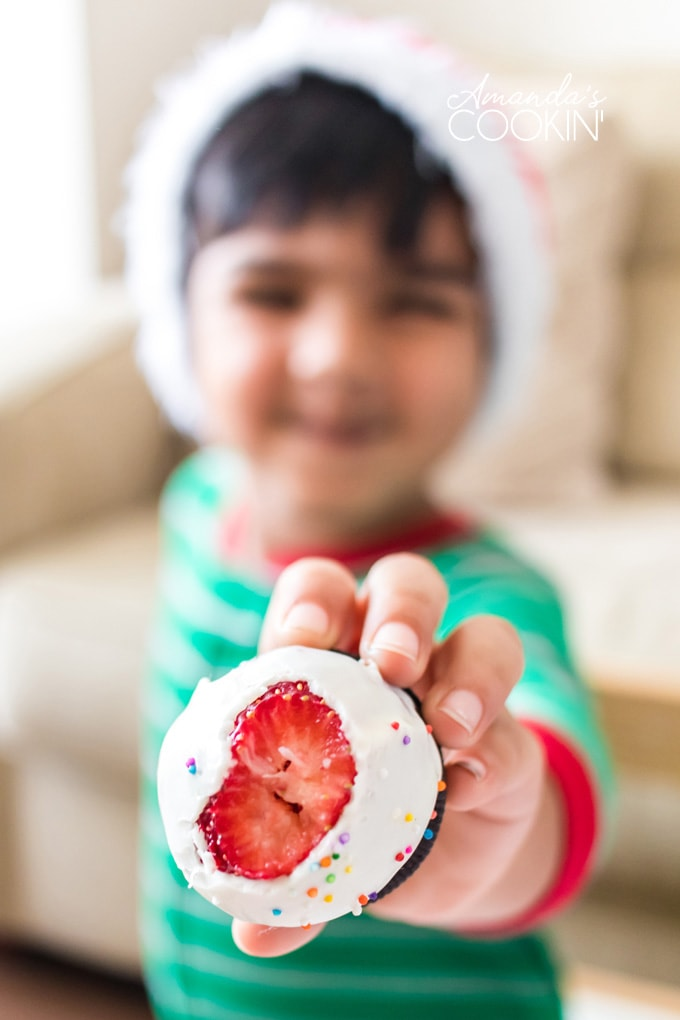 little boy holding out a chocolate covered strawberry with a bite out of it