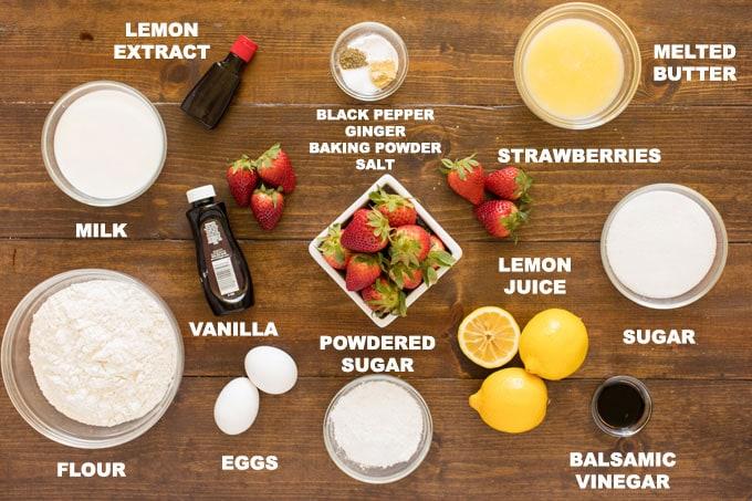 labeled ingredients for fresh strawberry muffins: flour, sugar, eggs, butter, black pepper, baking powder, ginger, salt, balsamic vinegar, strawberries, lemons, vanilla and lemon extract, powdered sugar, milk