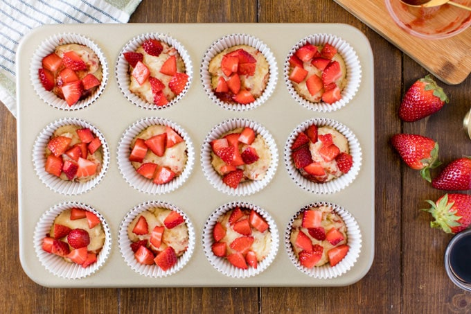 chopped strawberries on top of muffin batter in muffin tin