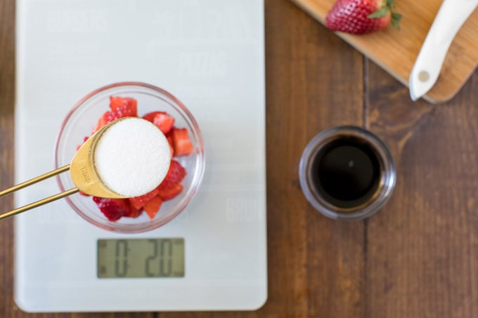 measuring spoon with sugar hovering over bowl of strawberries on a kitchen scale