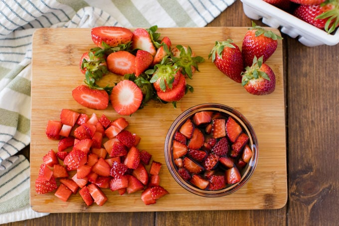 chopped strawberries and bowl of macerating strawberries on a cutting board
