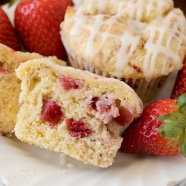 strawberry muffin sliced in half showing strawberries inside