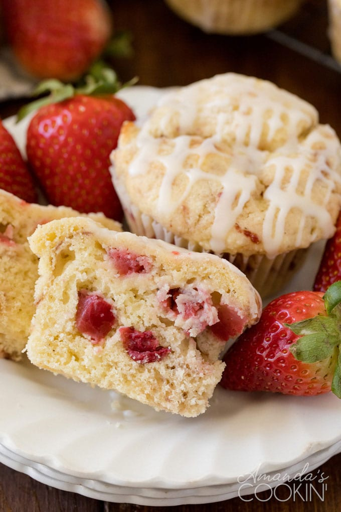muffin on a plate cut in half showing strawberries inside