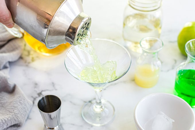 pouring shaken appletini into martini glass