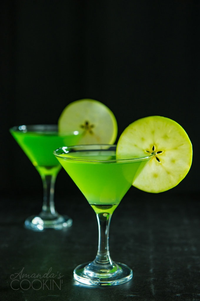 two appletini martinis on a dark background garnished with apple wheels