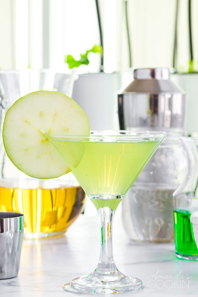 appletini in a martini glass with ingredients in the background