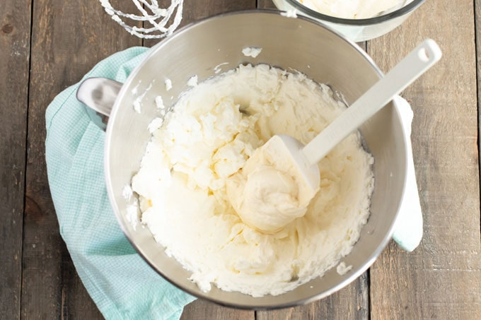 Folding frosting ingredients together in a bowl with a rubber spatula
