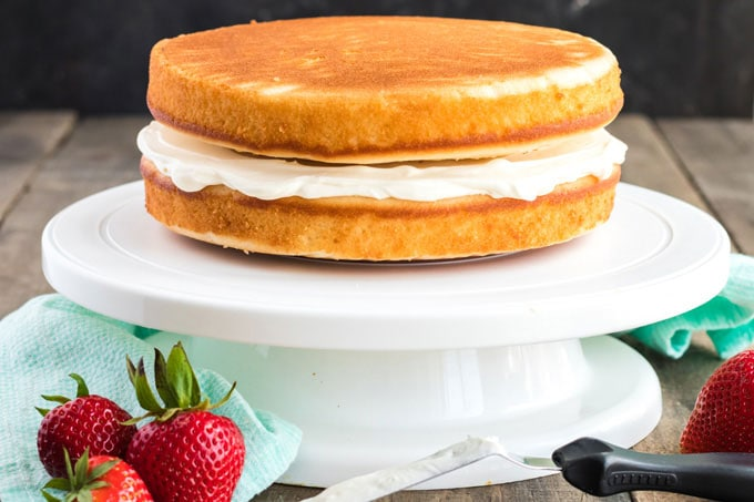 two cake layers with cream cheese frosting in between on a cake platter