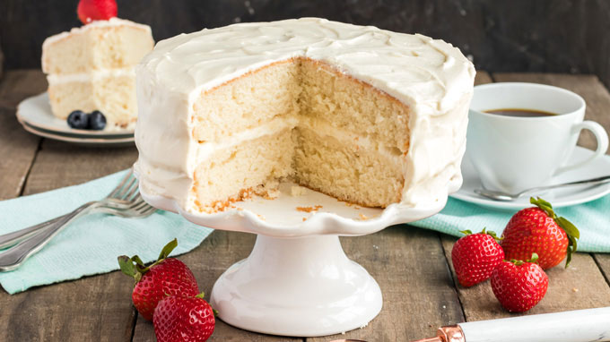 white cake with two slices removed sitting on a cake plate