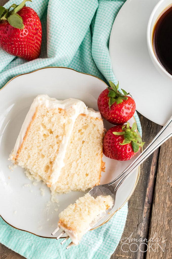 slice of white cake on a plate with strawberries and a fork