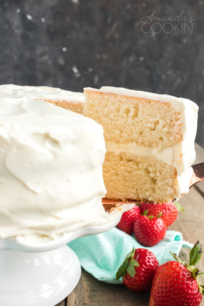removing a slice of white cake from platter