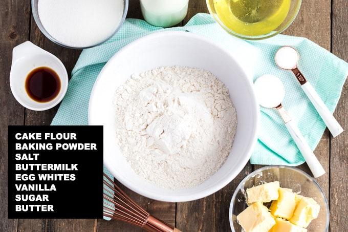 labeled ingredients for white cake recipe: cake flour, baking powder, salt, buttermilk, egg whites, vanilla, sugar, butter