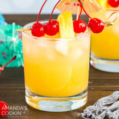 A glass of Mai Tai cocktail with cherry and pineapple garnish