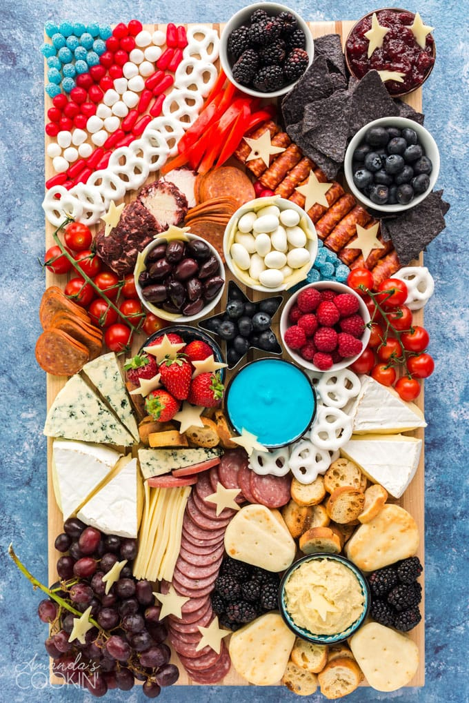 patriotic charcuterie board with tons of finger foods, cheese, crackers, fruit, etc