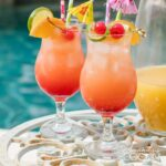 two glasses of rum punch poolside with a pitcher