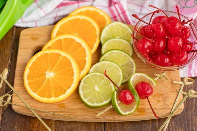 sliced oranges and limes with maraschino cherries on a cutting board