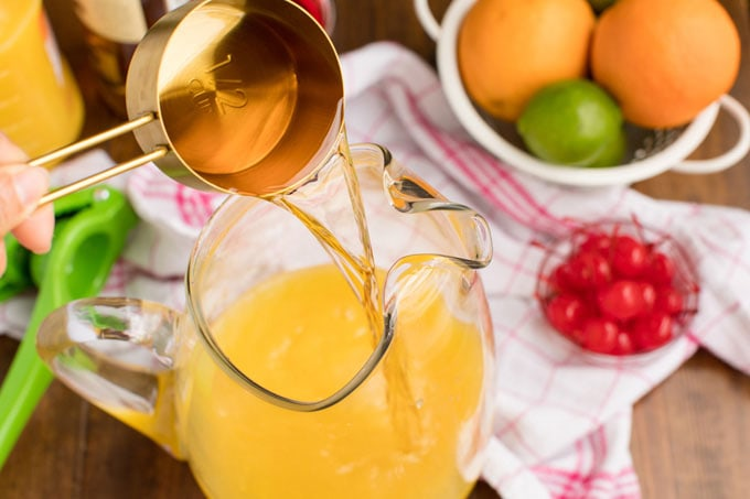 pouring rum into a pitcher of orange and pineapple juice