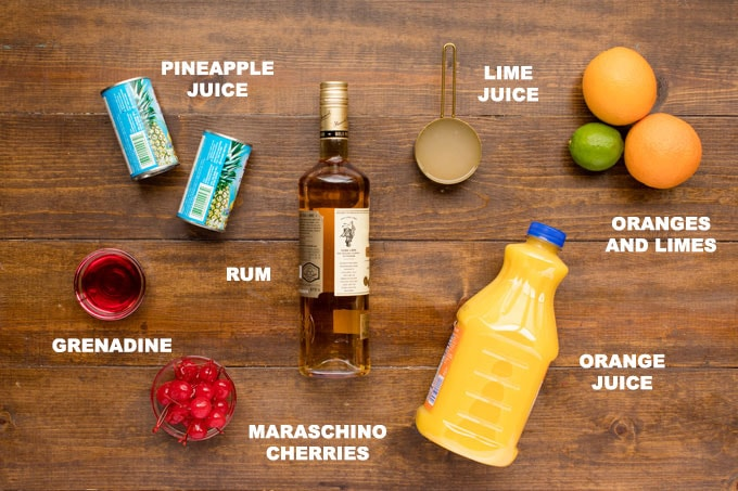 ingredients for rum punch, pineapple and orange juices, lime juice, rum, and garnishes