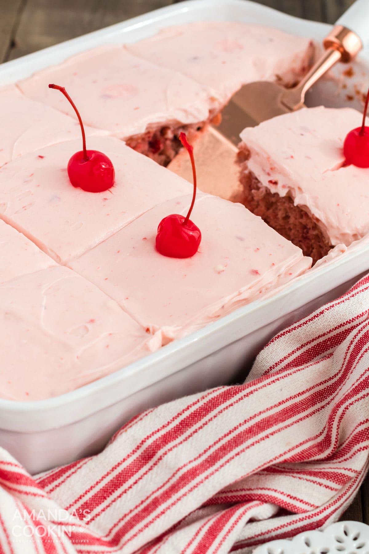cherry cake with cherry frosting and maraschino cherries for garnish