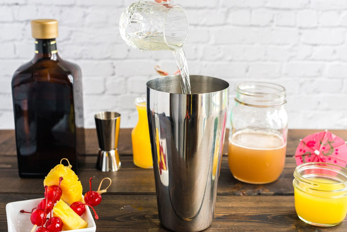 pouring rum into cocktail shaker