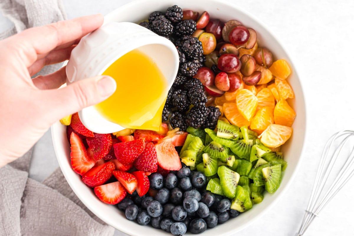 adding fruit juice dressing to bowl of fruit