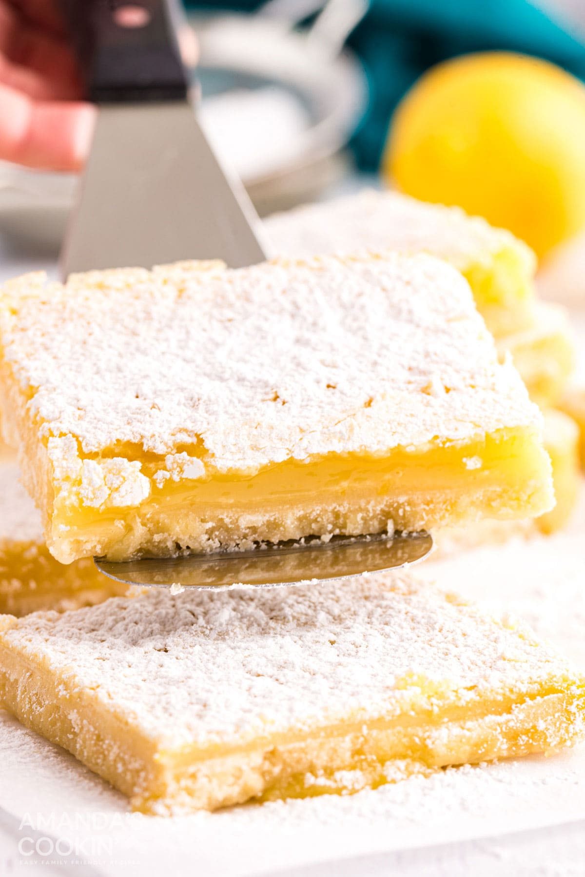 lemon bar being lifted with spatula
