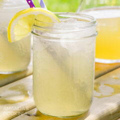 Mason jar glass of Lynchburg lemonade with a straw and lemon wedge garnish.
