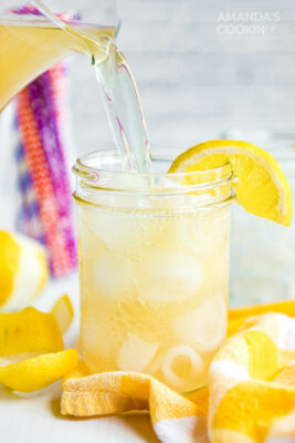 pouring Lynchburg lemonade into a mason jar glass form a pitcher