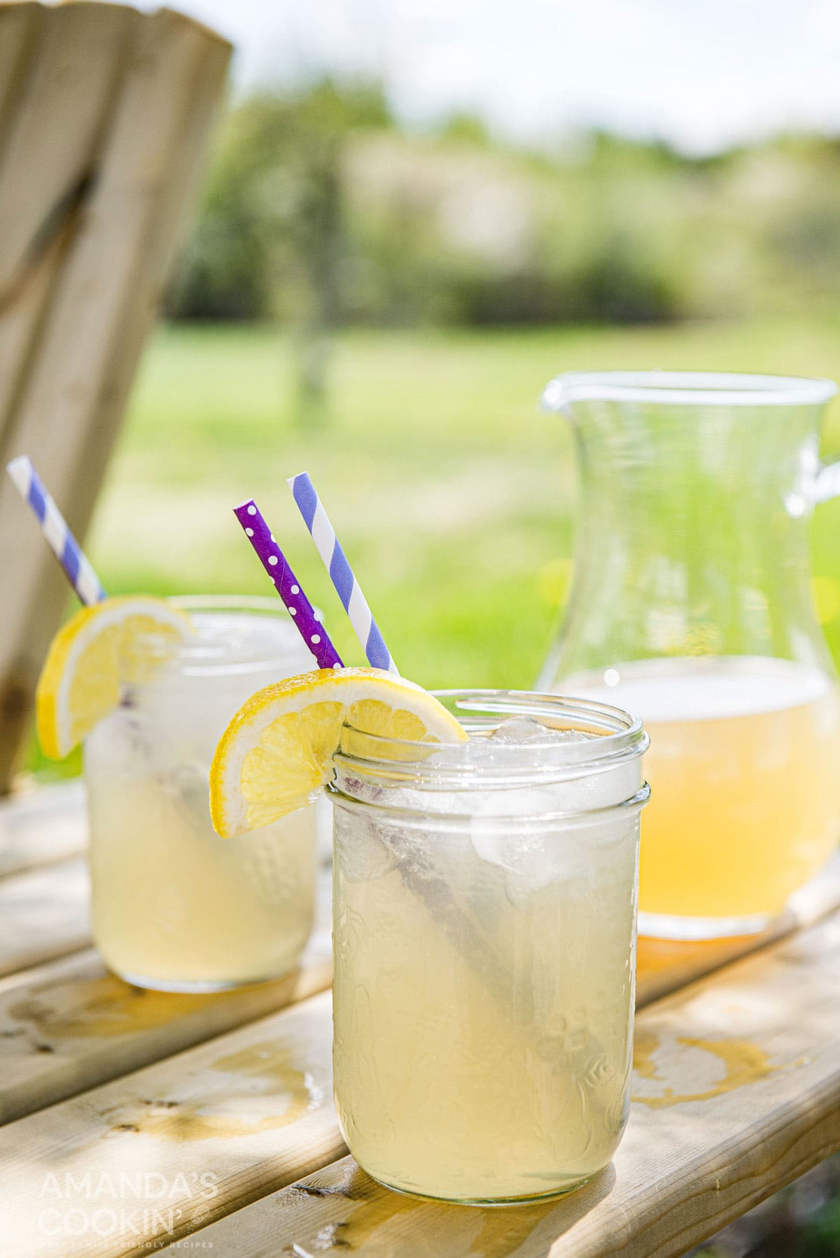 mason jars filled with lynchburg lemonade on an outdoor table with pitcher in the background