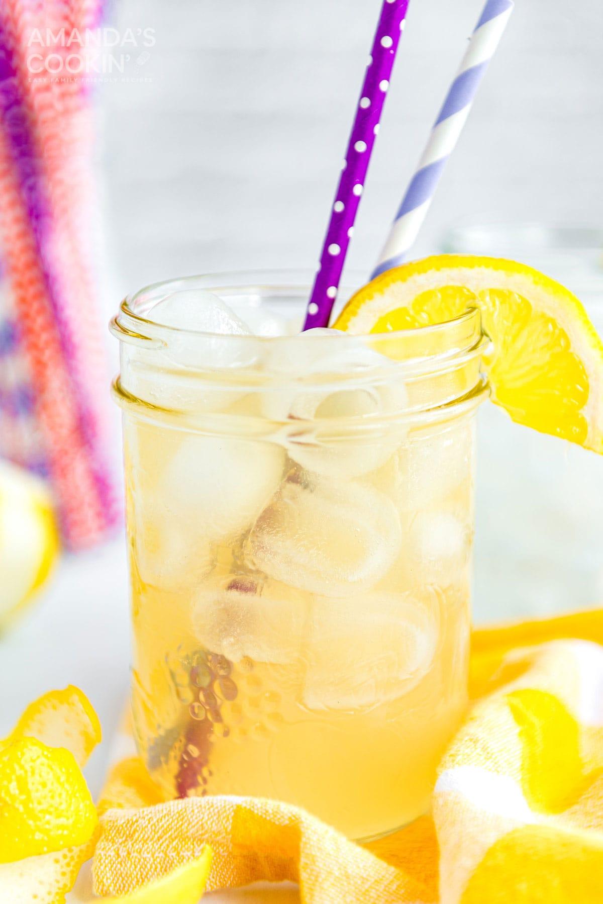 mason jar glass of lynchburg lemonade with straws and a lemon garnish