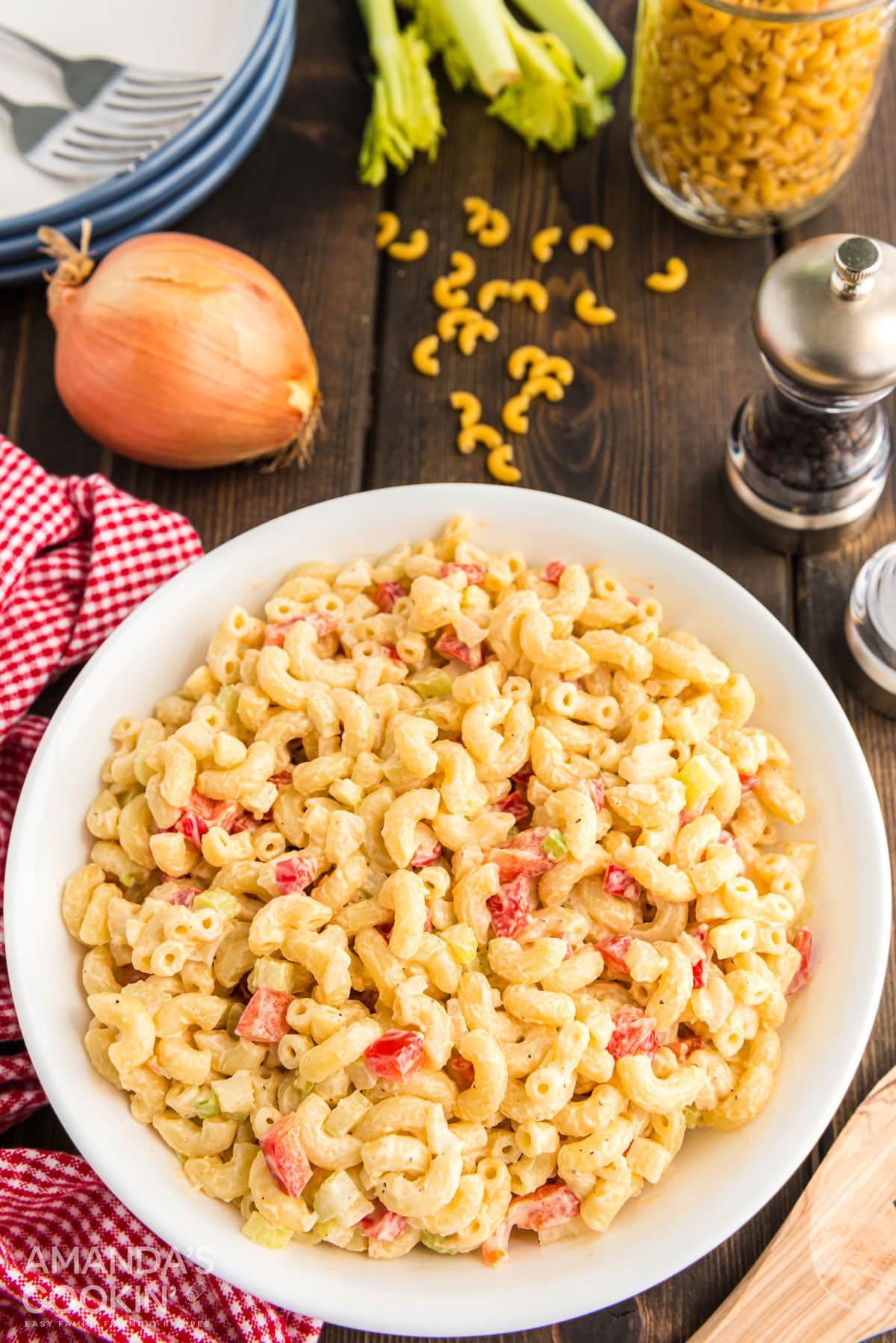 bowl of macaroni salad on a table with pepper, onion, dried pasta, and plates in background