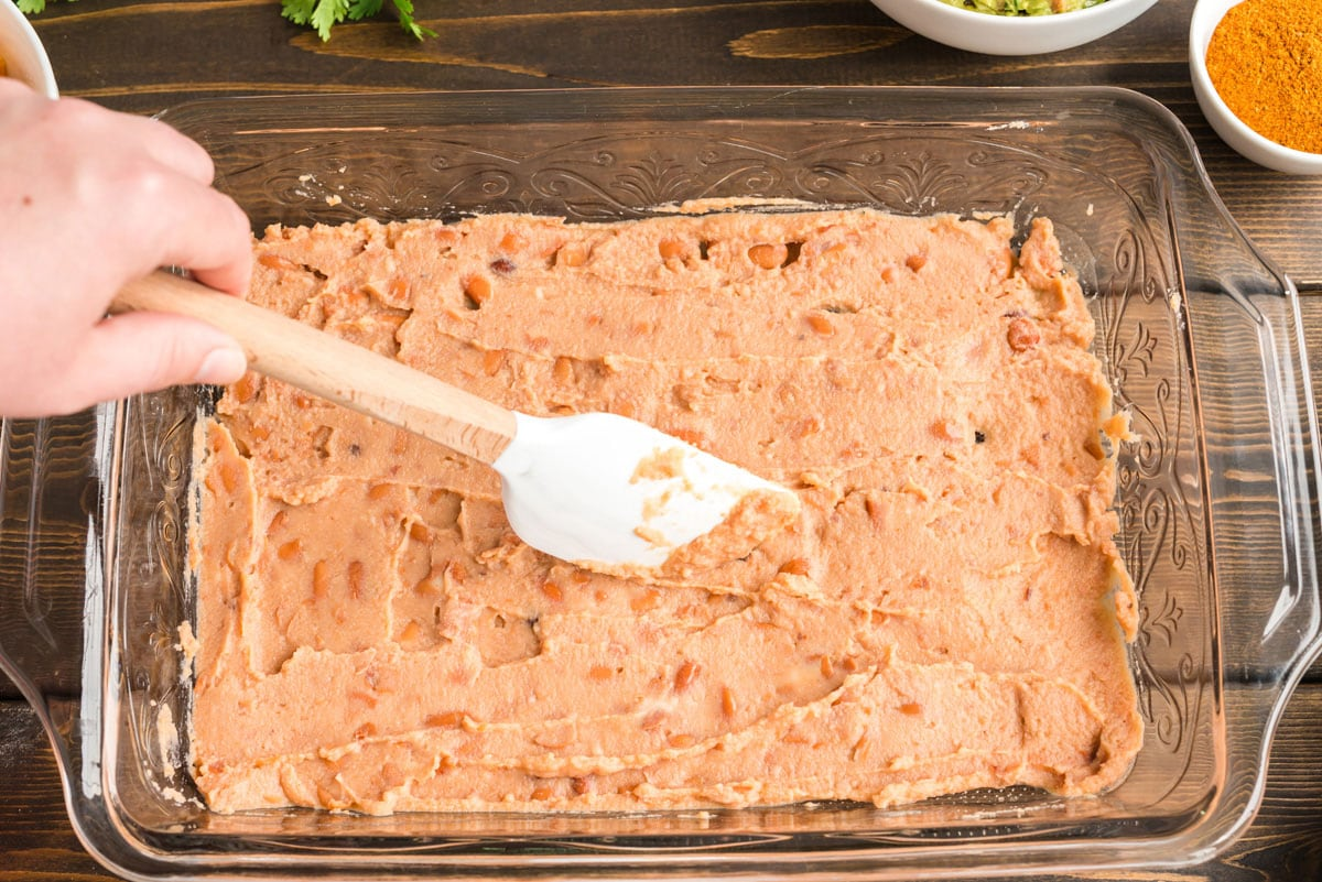 spreading refried beans in a glass pan