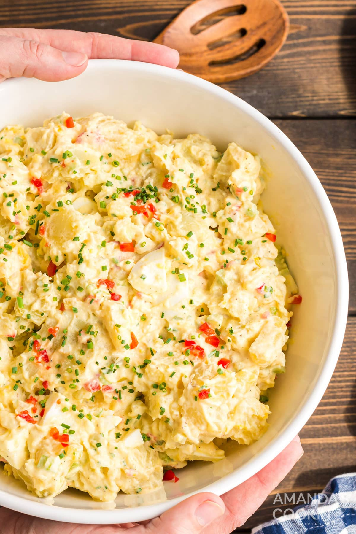 hands around large bowl of potato salad