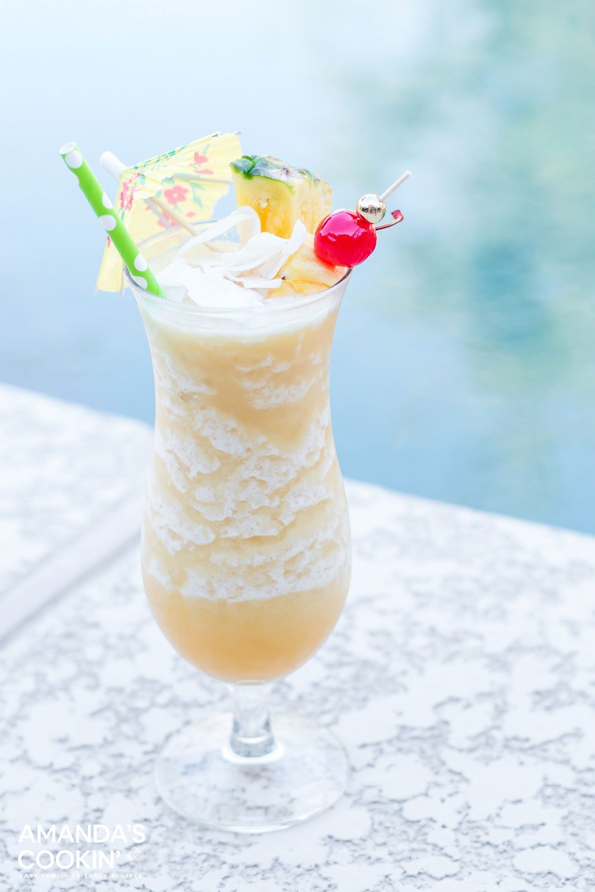 a frosty pina coloada drink sitting by the pool