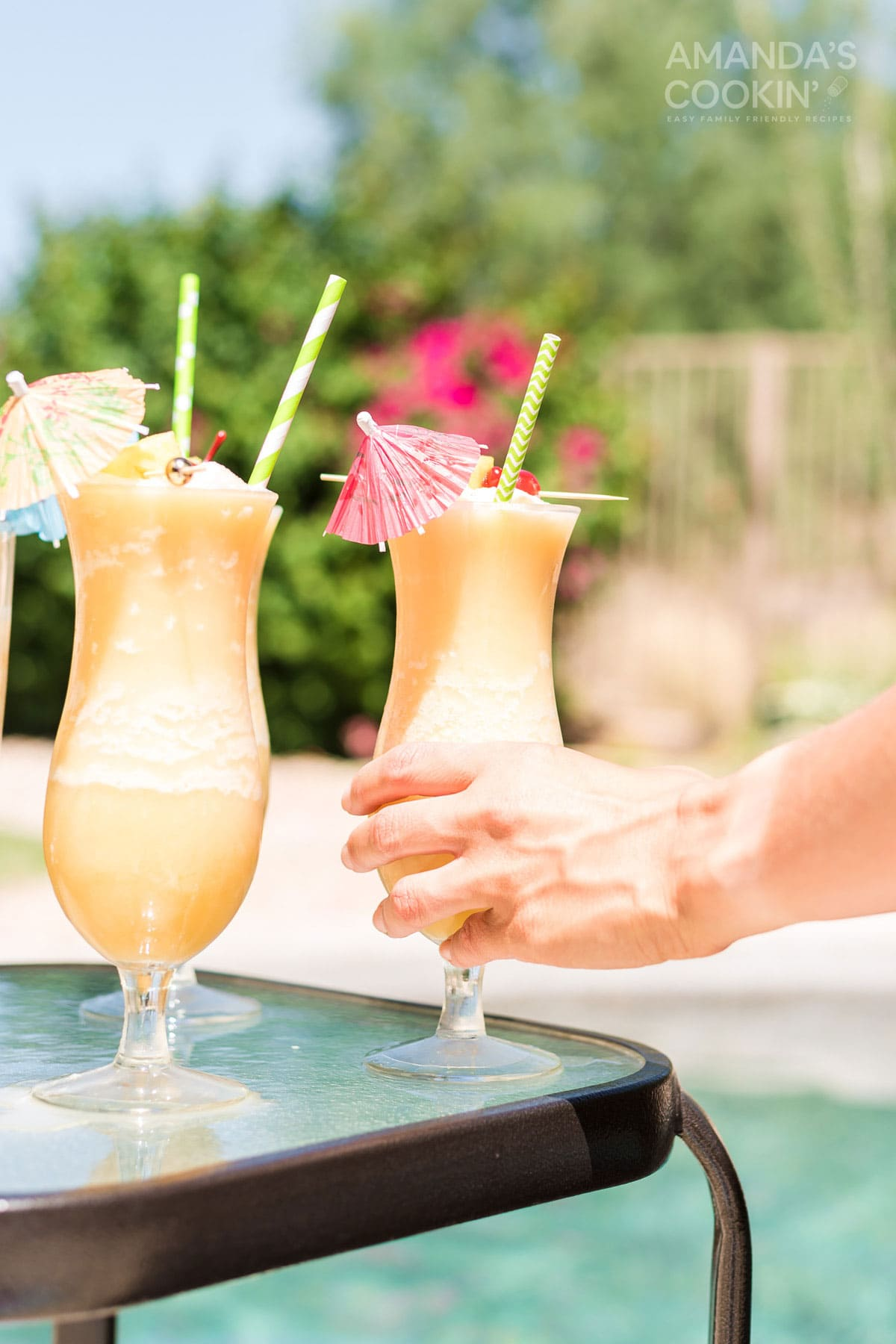 hand reaching for and picking up a pina colada cocktail by the pool