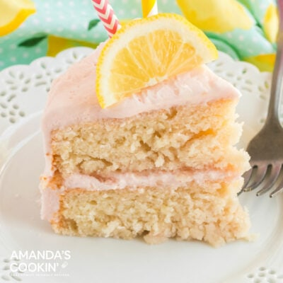 slice of pink lemonade cake with a slice of lemon on top