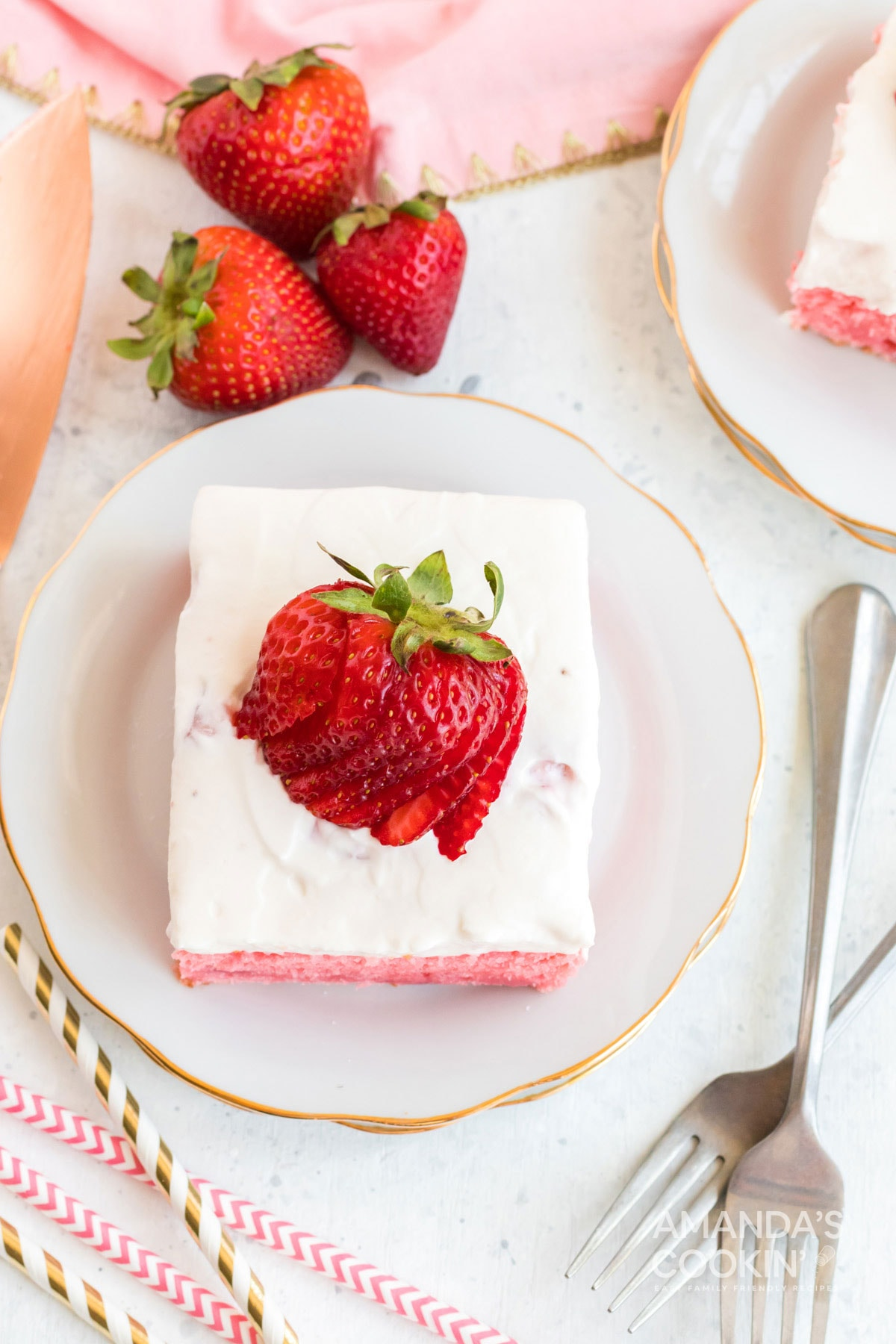 overhead photo of strawberry cake slice with fanned strawberry garnish
