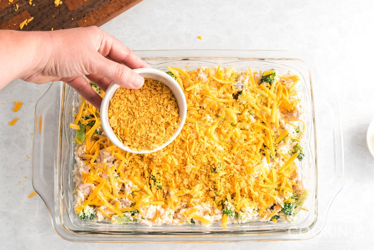 adding crushed corn flakes to Make Chicken Broccoli Rice Casserole