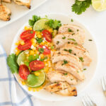 sliced cilantro lime chicken on a plate with corn and tomatoes