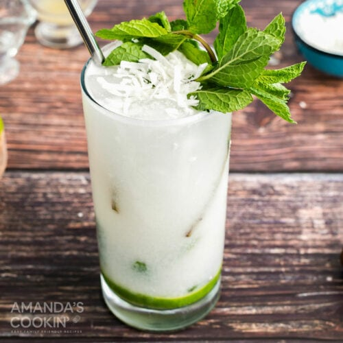 coconut mojito garnished with fresh mint and coconut flakes