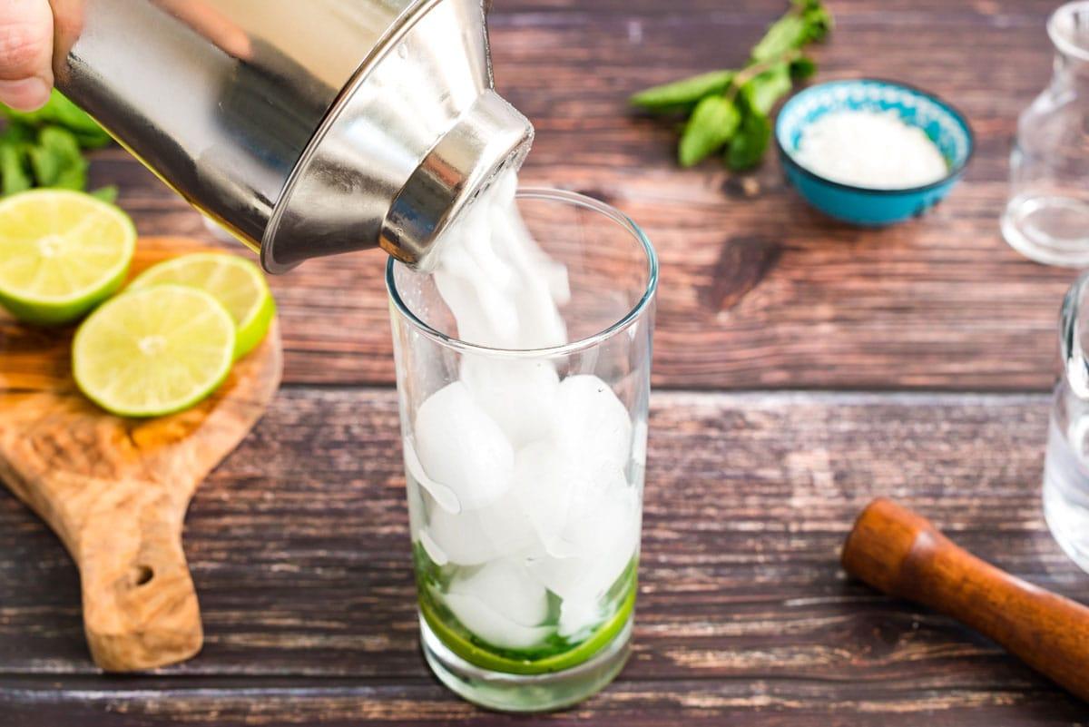straining coconut mojito into a glass
