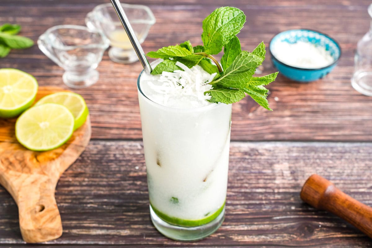 glass of coconut rum mojito garnished with mint and coconut flakes