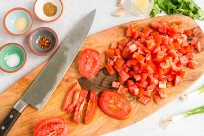 chopped tomatoes and a chefs knife on a cutting board